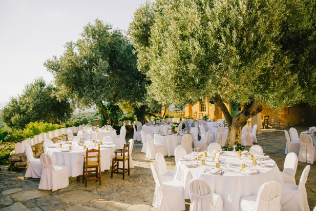 Detail of luxury elegant dinner reception set up in green, white and gold at Grecotel Agreco wedding estate in Crete captured before the arrival of guests and the grand entrance.