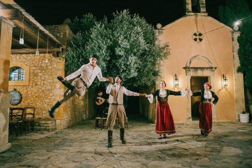 Greek dancers performing for wedding photographer and wedding guests during reception in Grecotel Agreco farm estate.
