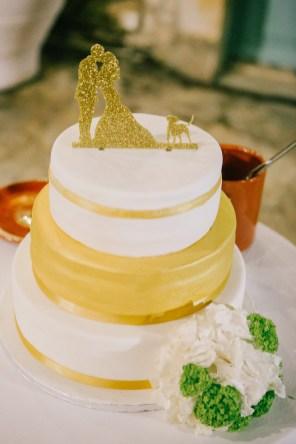 Artisan wedding cake professionally photographed against the background of stony walls and blue Greek windows of Grecotel Agreco farm.