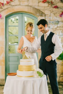 Groom and bride cutting the wedding cake and smiling with the background of stony walls and blue Greek windows of Grecotel Agreco farm.