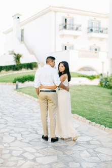 Engaged couple walking along a luxury tourist resort in Crete during their pre wedding engagement photosession at sunset.
