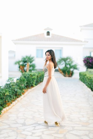 Engaged woman posing for portraits in a luxury tourist resort in Crete during the pre wedding engagement photoshoot.