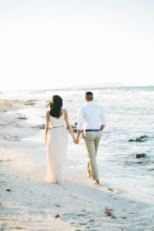 Engaged couple walking along the beach in Crete during their pre wedding engagement photosession at sunset.