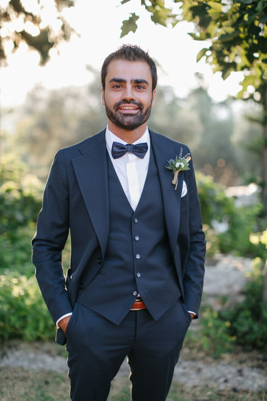 Fine art portrait of a trendy groom on his wedding day, styled and photographed in Dourakis winery in Chania Crete by professional wedding photographer team.