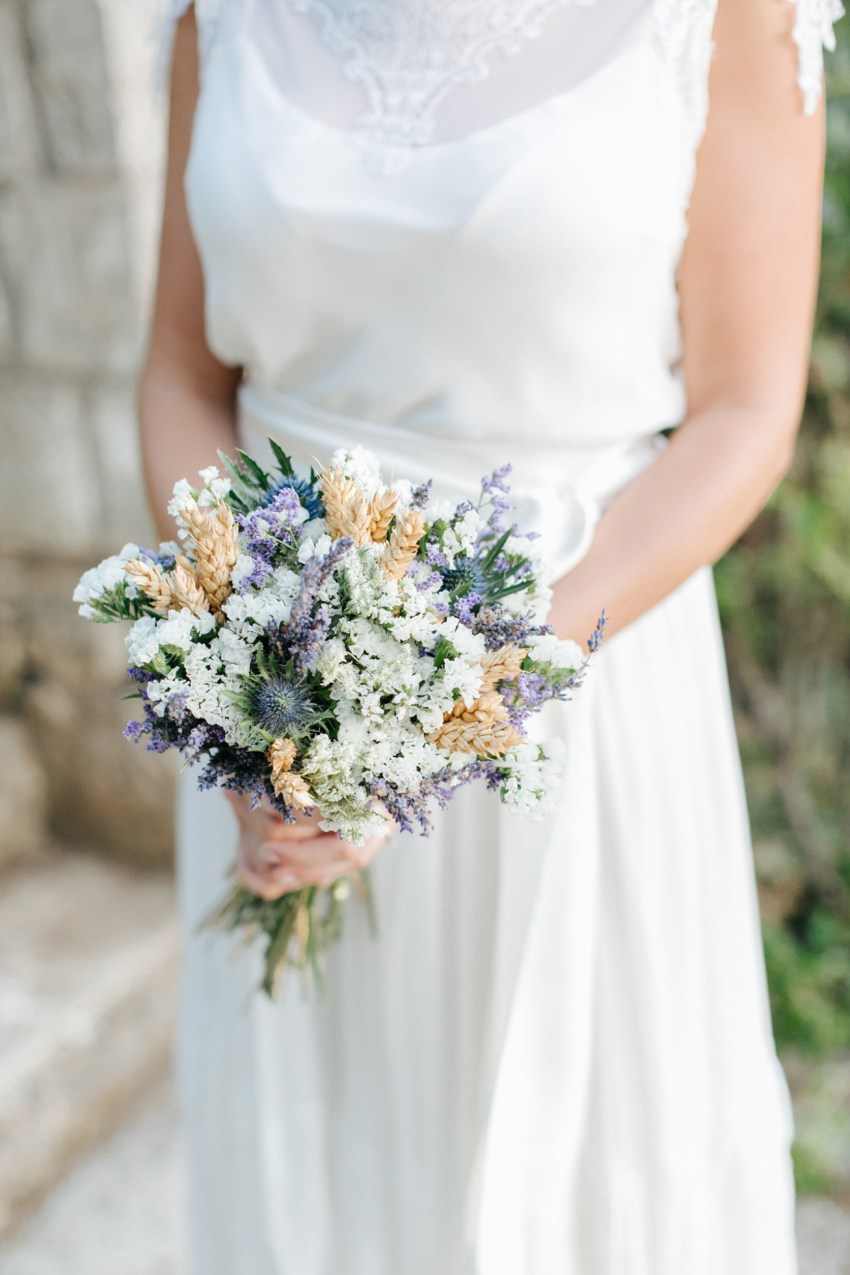 Intricate details of a beautiful trendy bride's bouquet and bridal dress on her wedding day, bride is posing for photos in Dourakis winery in Chania Crete captured by wedding photographer team.