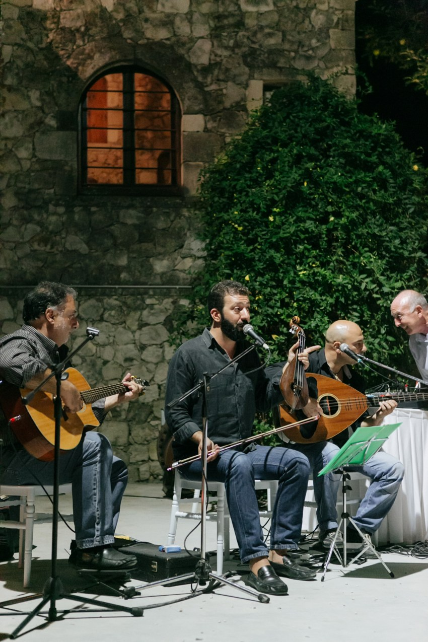 Evening image of traditional wedding day live Greek music band performing at the reception, photographed in Dourakis winery in Chania by professional wedding photographer team.