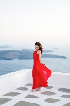 Beautiful Asian woman from Hong Kong is posing for the wedding photographer for her sunset engagement portrait in Imerovigli village Santorini. She's playfully smiling and wearing stunning red formal dress, standing on an elevated white balcony with the sea view in the background.