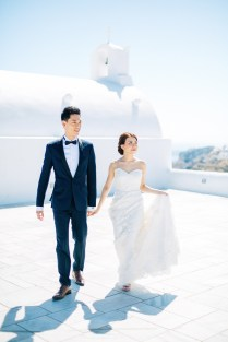 Professional Santorini wedding day photoshoot, groom and bride are walking with the picturesque background of Oia, white church, seaview and clear blue skies.