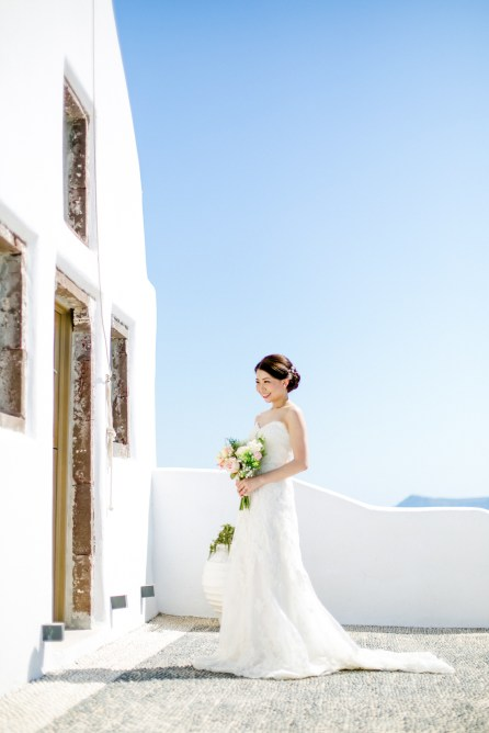 Professional Santorini wedding day photoshoot, bride is posing in front of the church holding flowers with the picturesque background of Oia and clear blue skies.