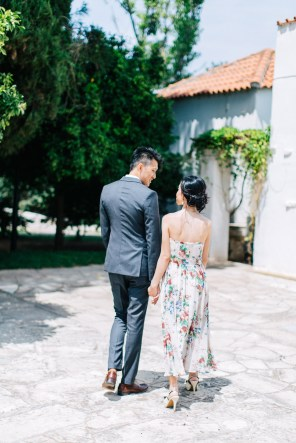 Young elegant couple wearing summer outfits is posing for their elopemement portraits for professional photographer team in Crete island, Greece. Colorful garden and park backdrop adds to the happy and vibrant feel of this session.