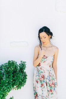 Young elegant woman wearing summer dress and elegant makeup is posing for her elopemement portraits for professional photographer team in Crete island, Greece. Colorful garden and park backdrop adds to the happy and vibrant feel of this session.