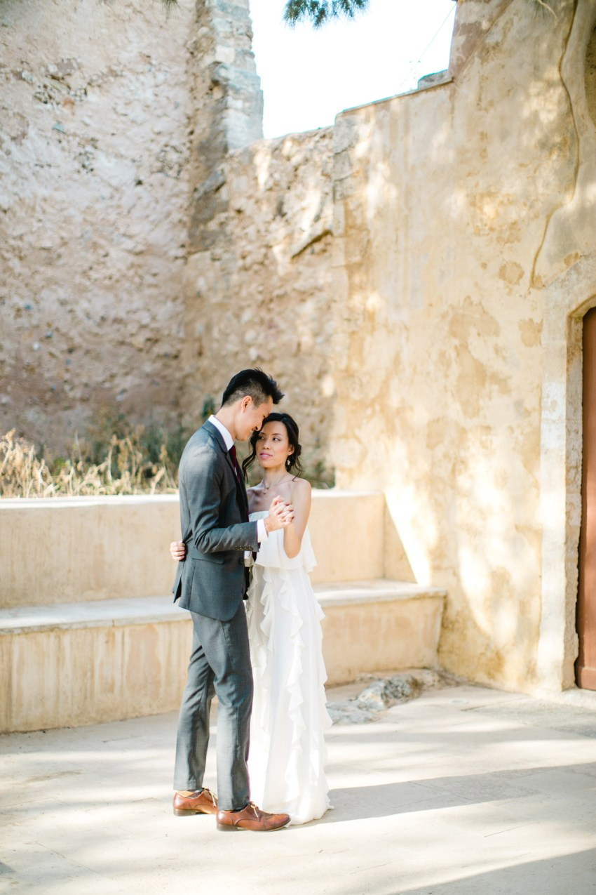 Elegant Asian couple wearing designer wedding clothing posing for professional photographer team during their wedding day photoshoot in Fortezza of Rethymno town, Crete.