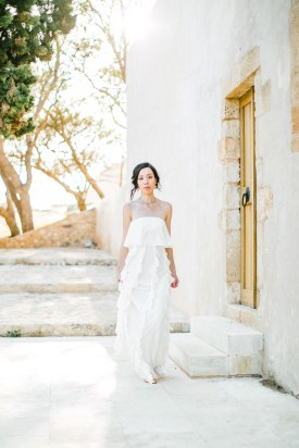 Elegant Asian bride wearing white understated and posh bridal dress posing for professional photographer for her wedding portraits in Fortezza of Rethymno town, Crete.
