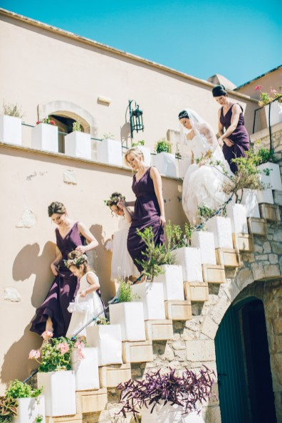 Candid image of an elegant bride and her bridesmaids walking down the stairs into the wedding ceremony on a destination wedding day in Agreco Farm in Crete.