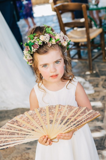 Beautiful flower girl holding a flower bouquet by Fabio Zardi posing for a fine art portrait on a wedding day in Agreco Farm in Crete.