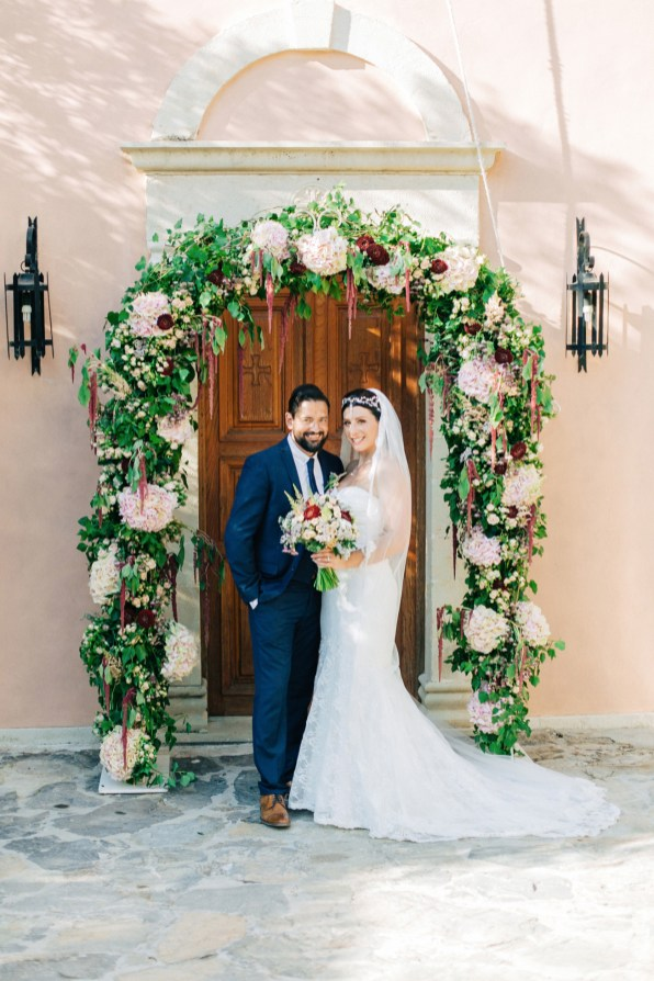 Stunning and happy bride and groom posing for portraits for their photographer on a destination wedding day in Agreco Farm, Crete.