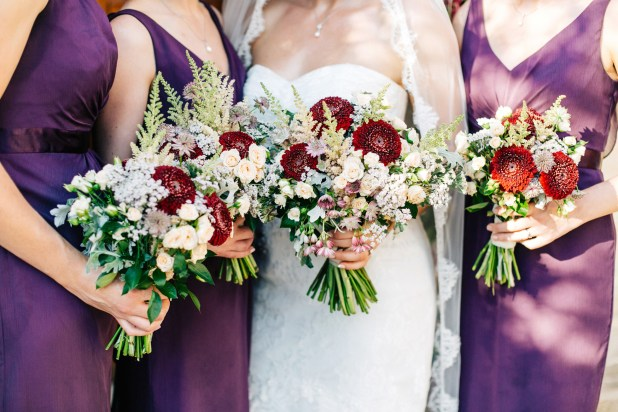 Stunning bride and her classy elegant bridesmaids wearing matching purple dresses and holding flower bouquets posing for formal portraits after the wedding ceremony at Agreco Farm in Crete, Greece.
