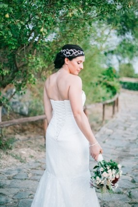Stunning bride posing for portraits for her photographer on a destination wedding day in Agreco Farm, Crete.