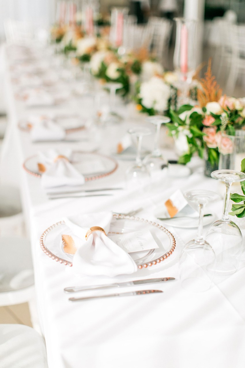 Wedding dinner details and reception decoration in white and blush pink at Le Ciel wedding estate in Santorini island, Greece.