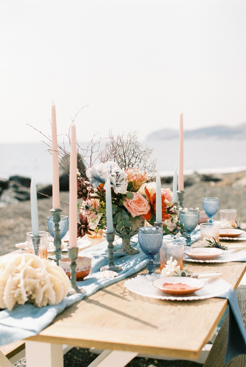 Vibrant wedding dinner and reception beach table setup in Santorini accented with coral and exotic florals.