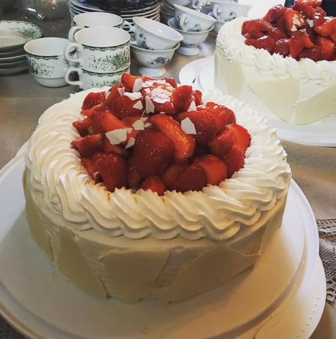 Gräddtårtor med smakerna hallonmousse och citronkräm toppad med jordgubbar och vitchoklad