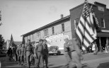 Mauston Boy Scouts enter the parade line, circa 1943. The town's military honor roll can be seen on the side of the building.