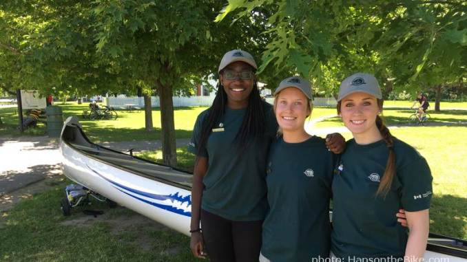 Parks Canada staff Adonaelle, Elisha and Tara in front of 'their' Voyageur canoe.