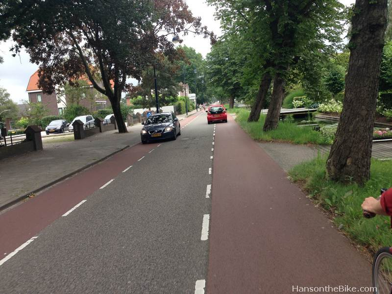 Stommeerweg (Stom-meer-weg) in Aalsmeer, Netherlands. Note how the cars pass using the advisory lanes. Once passed, they will return to the middle of the road, leaving the bike lanes for cyclists.