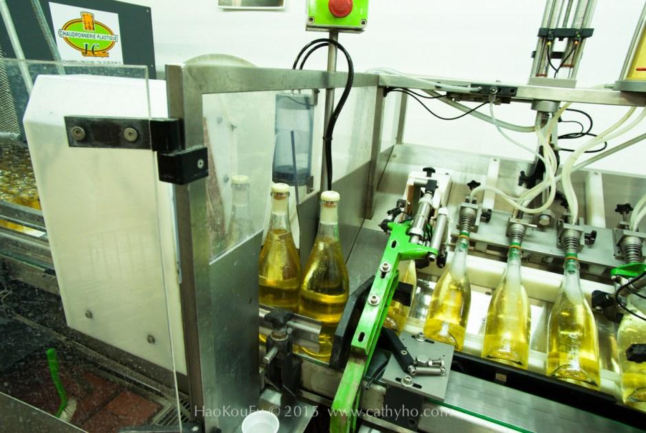 正要進行除渣的香檳,瓶口的酒渣已冷凍結冰,用機器開瓶除渣後,隨即進入加糖和補酒的程序