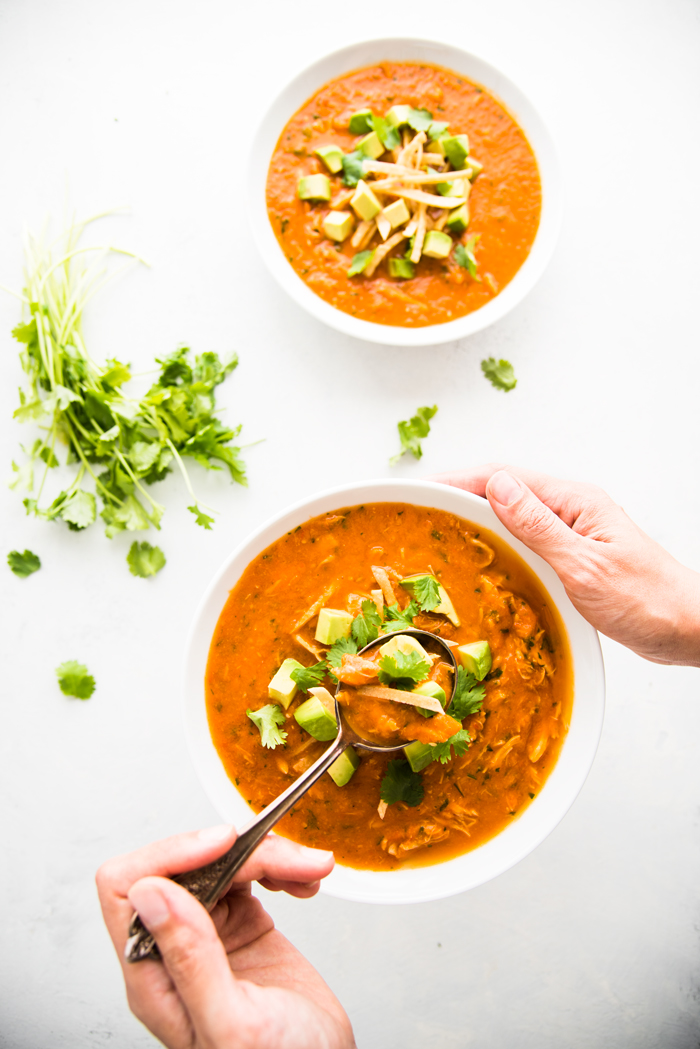 Easy and healthy Chicken Tortilla Soup made with fresh tomatoes and topped with avocado and crispy tortilla strips.