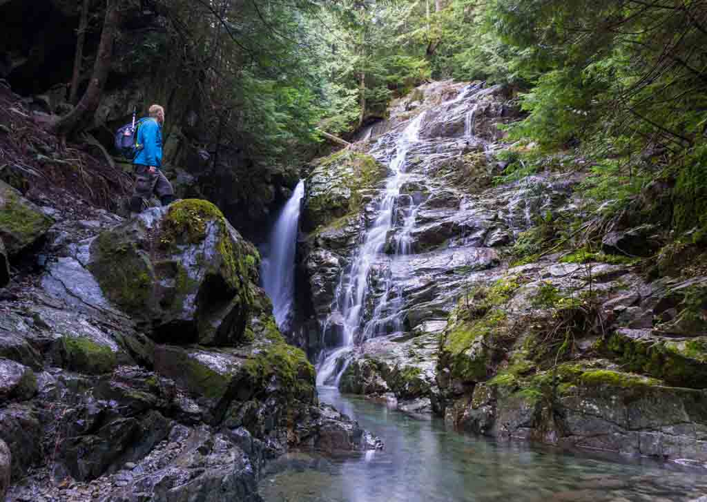 A hiker stands next to Kennedy Falls in North Vancouver, BC