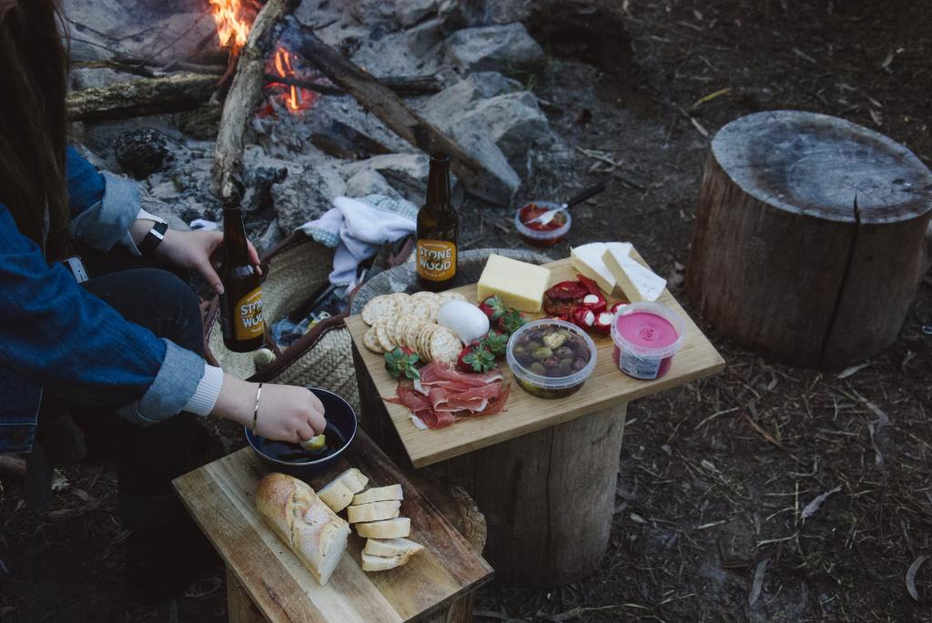 A charcuterie board next to a campfire. One of the best Valentine's ideas for outdoorsy couples: go on a backcountry dinner date