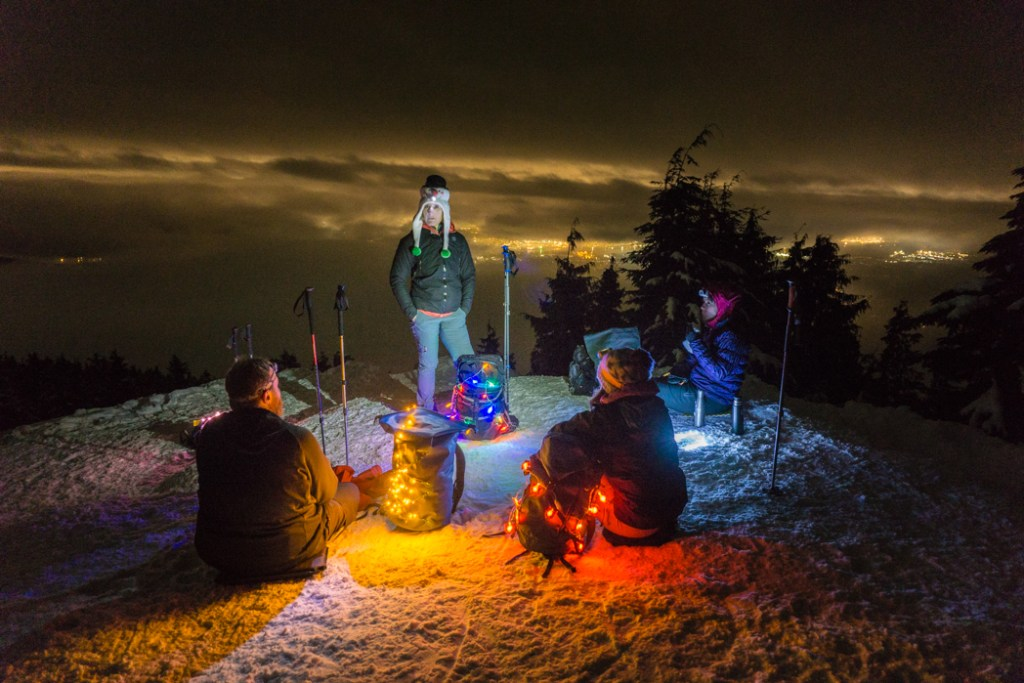 Hikers on a mountain top at night. Don't like crowds? Here are 15 ways to avoid crowded hiking trails.