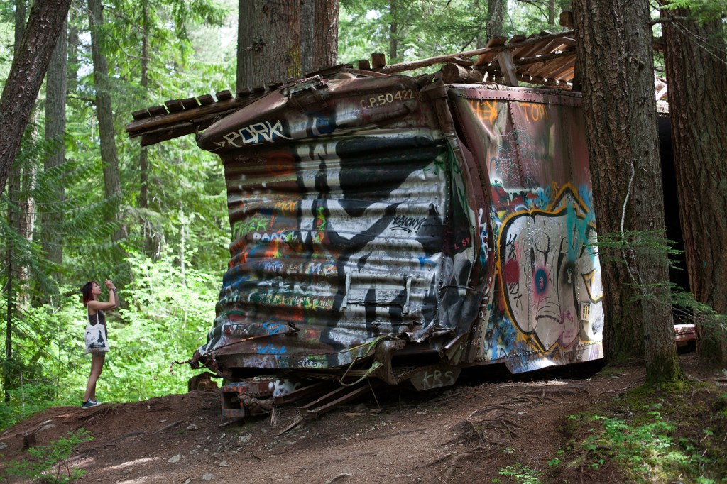 A graffiti covered train car on the Whistler Train Wreck trail. Just one of 15 unusual hikes near Vancouver.