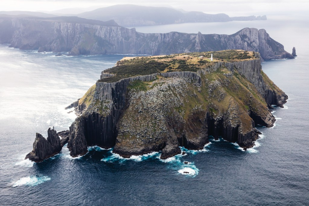 An aerial view of Tasman Island near Port Arthur, Tasmania, Australia. Taking a helicopter tour is one of the best ways to see the Tasman Peninsula and Port Arthur