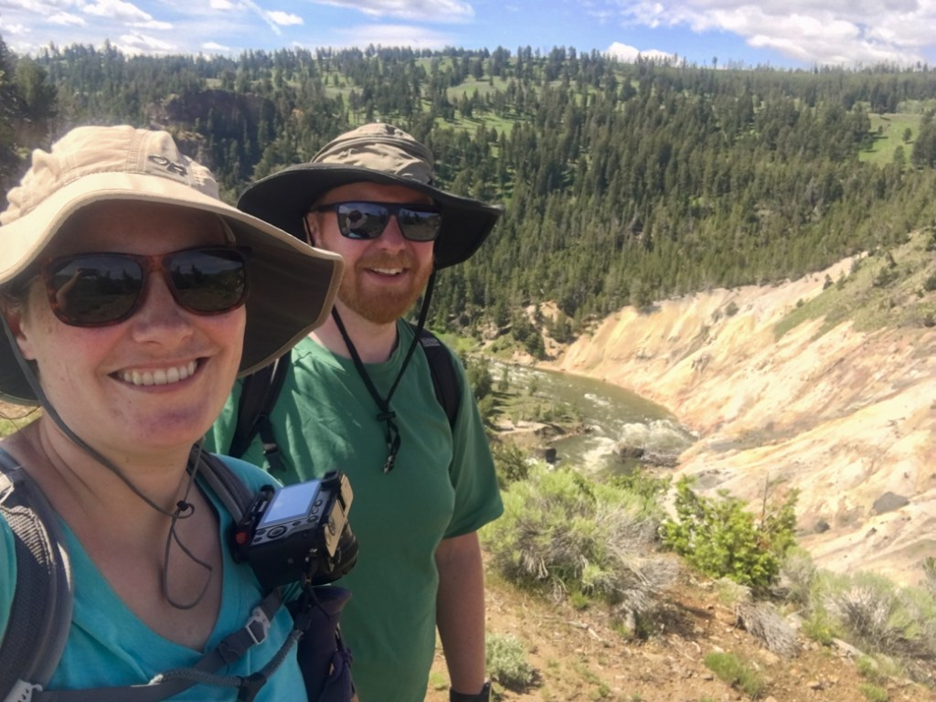 Two hikers wearing wide-brimmed hats and sunscreen in Yellowstone National Park. Make sure to put sun hats on your Yellowstone packing list.
