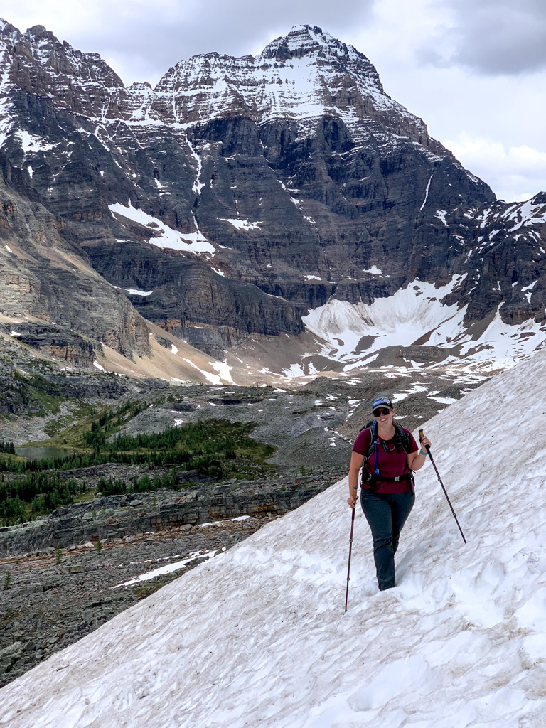 A hiker crossing snow on the All Soul's Alpine Route at Lake O'Hara in Yoho National Park