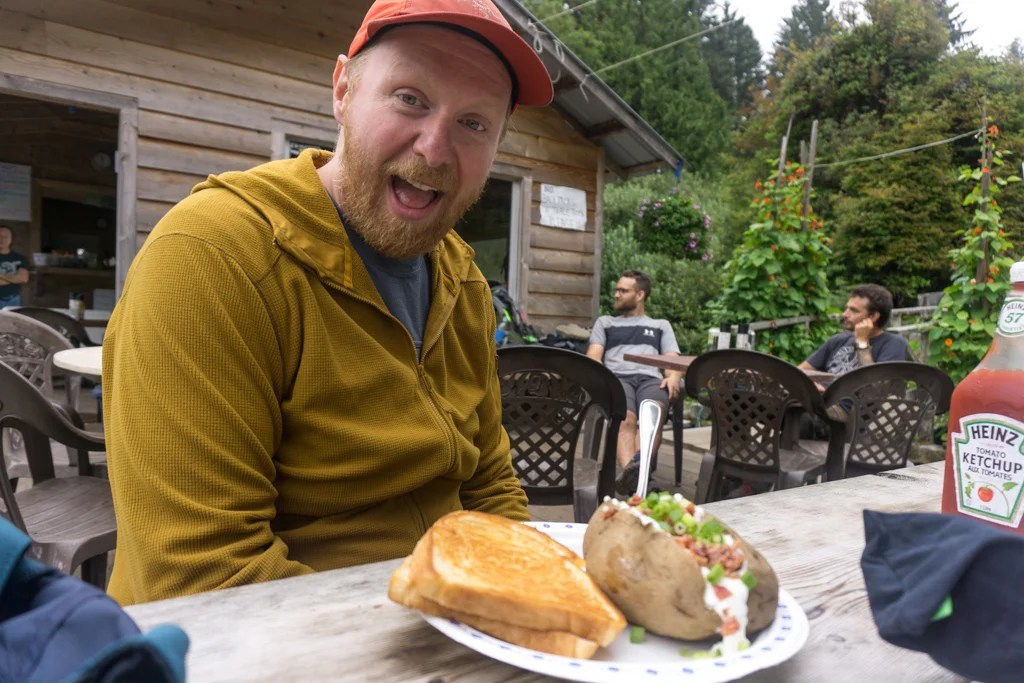 A hiker with a plate of food at The Crab Shack