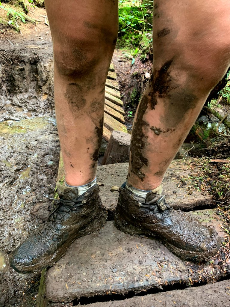 A hikers legs covered in mud on the West Coast Trail