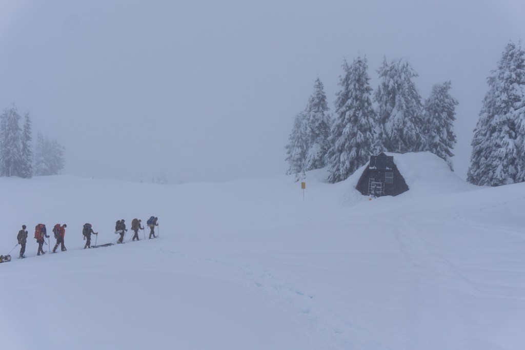A group of snowshoers walking through a snowstorm and fog to reach a backcountry hut