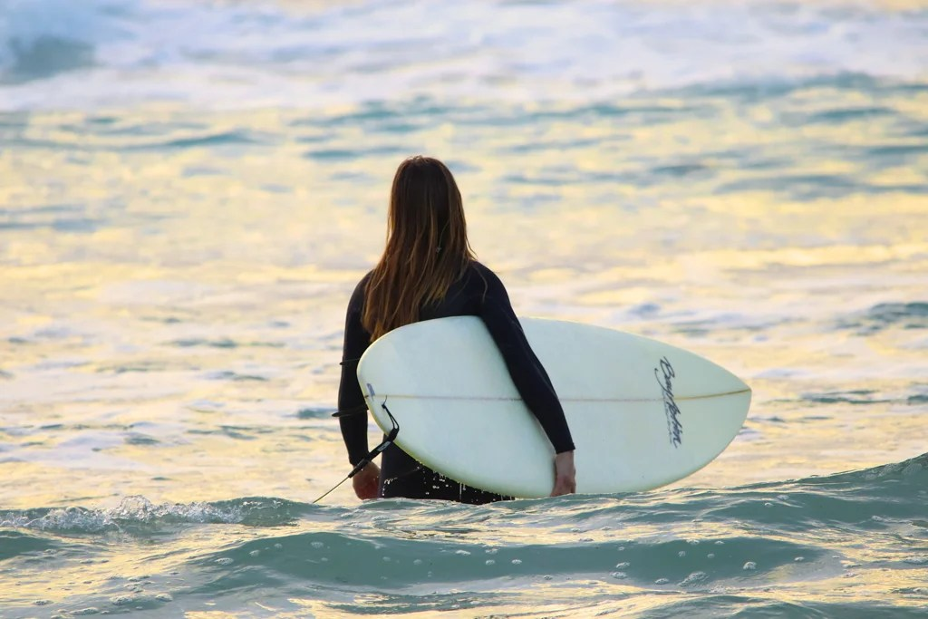 A woman in a wetsuit walks into the water holding a surfboard