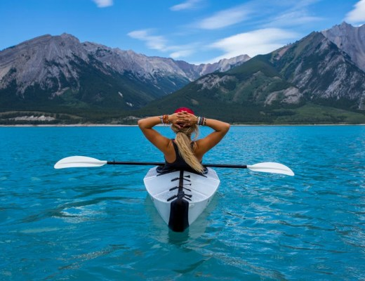 A woman sits in a kayak on a blue lake. Watch women's adventure films.