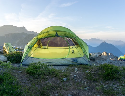 A tent on top of a mountain ridge with mountains in the background. A backpacking tent is one of the basic items on your backpacking checklist - things you should pack for a backpacking trip
