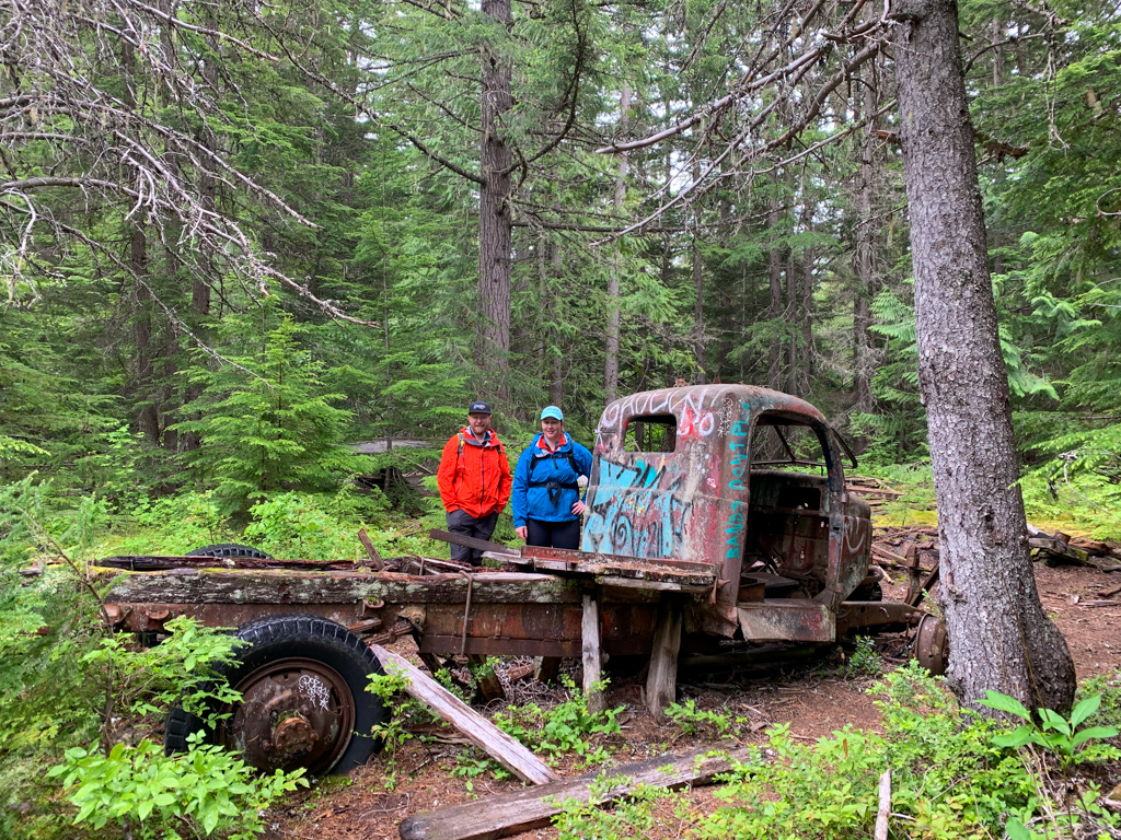 Two hikers next to an abandoned truck near Whistler, BC
