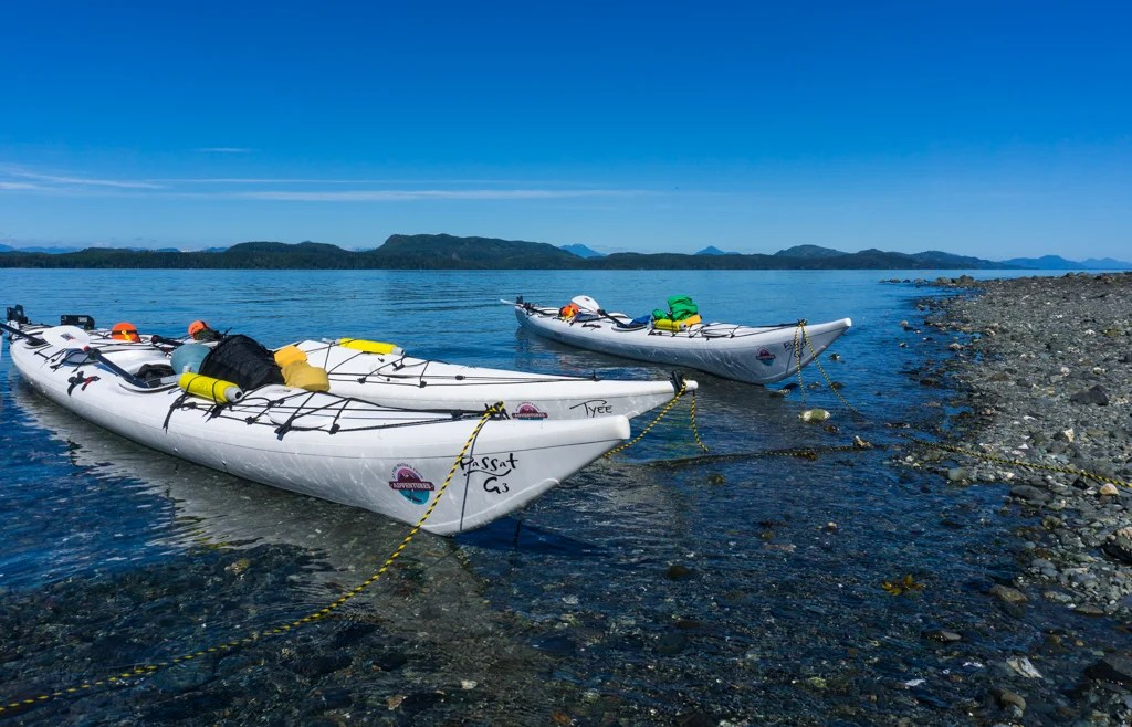 Three kayaks on the beach in the Johnstone Strait on Vancouver Island in British Columbia, Canada. Go kayaking in the Johnstone Strait