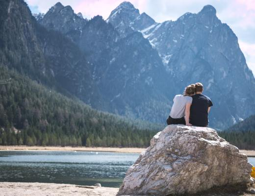 A couple sitting on a rock looking at a mountain view. The most romantic Valentine's gifts for hikers and campers