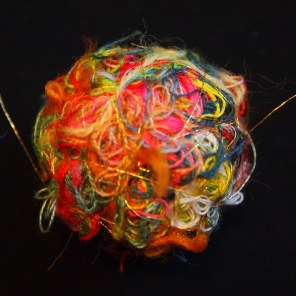 A brightly colored happify thread ball against a black background. This particular happify design has a tangle of wool, cotton, and miscellaneous threads, with a final layer of a very fine metallic gold thread strung around.