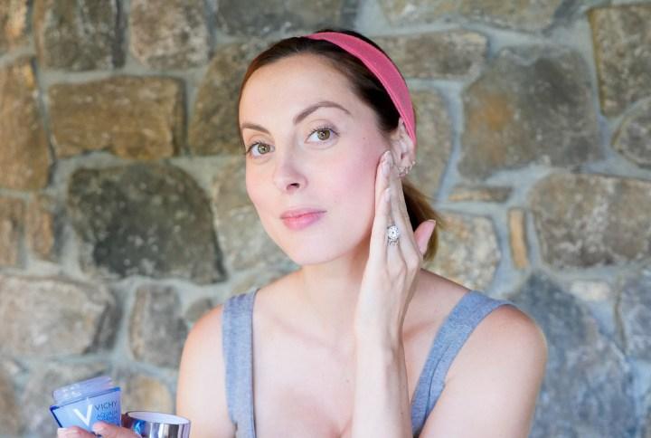 Eva Amurri Martino of lifestyle blog Happily Eva After applying a lightweight moisturizer to her bare skin