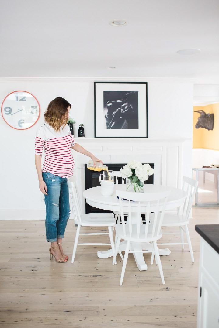 Eva Amurri Martino of lifestyle blog Happily Eva After pouring orange juice while wearing a red and white striped maternity top in her kitchen in connecticut
