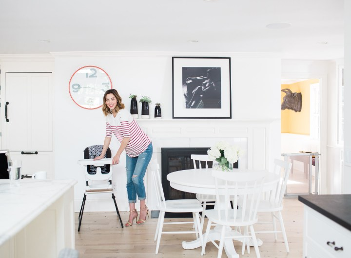 Eva Amurri Martino of lifestyle blog Happily Eva After at 36 weeks pregnant, wearing a red and white striped maternity top and jeans and interacting with the new Jonathan Adler crafted by fisher price collection high chair